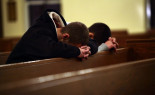 Two men pray at Saint Rose of Lima Roman Catholic Church near Sandy Hook Elementary School, where a gunman opened fire on school children and staff in Newtown, Connecticut December 14, 2012. Twenty schoolchildren were slaughtered by a heavily armed gunman who opened fire at a suburban elementary school in Connecticut on Friday, ultimately killing at least 27 people including himself in the one of the worst mass shootings in U.S. history.  REUTERS/Joshua Lott (UNITED STATES - Tags: CRIME LAW EDUCATION)