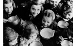 Circa 1946 in Greece, smiling girls of Patras, a north-western port city, eat their first UNRRA-provided meal from metal bowls. [THIS IMAGE PROVIDED COURTESY UN ARCHIVES. INFORMATION PROVIDED TO THE EXTENT AVAILABLE.]  The United Nations Relief and Rehabilitation Administration (UNRRA) was created in 1943 to assist with relief operations and global recovery from the devastation of World War II. Focusing primarily on Europe and China, it finally closed in 1949 as its mandate was subsumed in the long-term development work of other United Nations agencies. UNRRA's work for children was taken over by UNICEF, created on 11 December 1946.