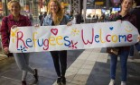 Girls-standing-with-sign-welcoming-migrants-70132